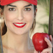 Young woman wearing red cap with apple in her hand — Stock Photo