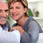 Smiling couple sitting on a sofa — Stock Photo