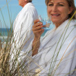 Stock Photo: Mature couple down beach in bathrobe.