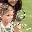 Girls looking through magnifying glass — Stockfoto