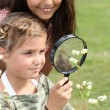 Foto Stock: Girls looking through magnifying glass