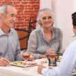 Young man and senior couple having a dinner in a restaurant — Stock Photo