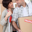 Couple moving into new home with boxes marked fragile - Stock Photo
