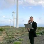 Businessman using a laptop on a windfarm — Stock Photo