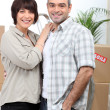A couple behind a pile of cartons inside a house — Stock Photo