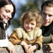 Young family leaning against fence - Stock Photo