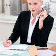 Blonde businesswoman writing a report — Stock Photo