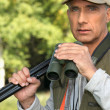 Hunter with a shotgun and pair of binoculars — Stock Photo