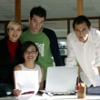 Royalty-Free Stock Photo: Young creative team standing with a laptop computer