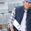 Construction worker with building plans and cellphone — Stock Photo