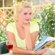 Woman sitting on a terrace with a glass of wine — Stock Photo