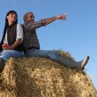 Portrait of a couple on a hay bale — Stock Photo