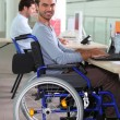 Young man in a wheelchair using a computer in the workplace — Stock Photo