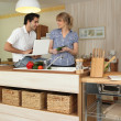 Young man and young woman smiling in kitchen — Stockfoto