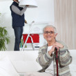 Young man fixing lamp for older woman — Stock Photo #9067280
