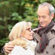 Old couple wearing warm clothes in forest and expressing tenderness — Stock Photo #9068658