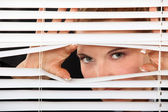 Woman peering through blinds — Stock Photo