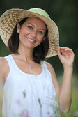 Attractive brunette in a summery straw hat — Stock Photo