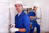 Dva kvalifikovaní živnostníci v modrých jumpsuites v prázdné místnosti — Stock fotografie