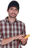 Handsome electrician using tester — Stock Photo