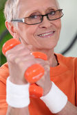 Older woman using dumbbells — Stock Photo