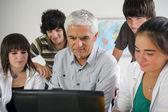 Teacher and pupils gathered around computer — Stock Photo
