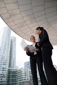Two businesswomen stood outside high-rise building — Stock Photo