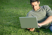 Man relaxing in field with laptop — Stock Photo