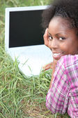 Young woman with a blank screened laptop in the grass — Stock Photo
