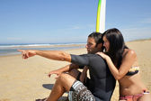 Couple of surfers pointing towards the sea — Stock Photo