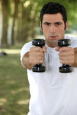 Man lifting weights in park — Stock Photo