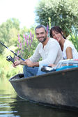 Couple fishing in a boat on a lake — Stock Photo