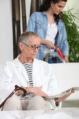 Young woman vacuuming next to senior woman — Stock Photo