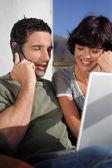 Par i solskenet med en bärbar dator och telefon — Stockfoto