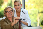 Starsza kobieta z pielęgniarką — Zdjęcie stockowe