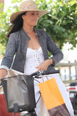 Woman on bike with shopping bags — Stock Photo