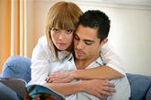 Man and woman embraced on a couch — Stock Photo