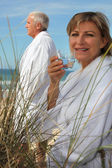 A mature couple down the beach in bathrobe. — Stock Photo