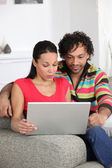 Couple at home looking at a laptop — Stock Photo