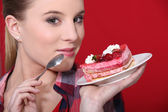 Woman holding up a scrumptious piece of cake — Stock Photo