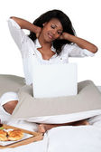 Black woman cross-legged on bed with laptop — Stock Photo