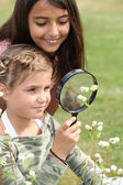 Girls looking through magnifying glass — Stock Photo
