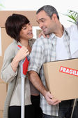Couple moving into new home with boxes marked fragile — Stock Photo