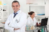 Smiling doctor cross-armed in lab — Stok fotoğraf