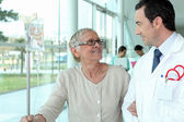 Doctor helping elderly patient in hall — Stock Photo