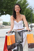 Woman on a pushbike laden down with store bags — Stock Photo