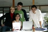 Young creative team standing with a laptop computer — Stock Photo