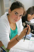 Teenage girl writing in an exam — Stok fotoğraf