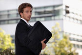 Young man with suitcase going to work — Stock Photo