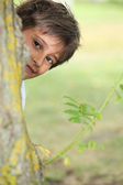 Young boy playing peek a boo around a tree — Stock Photo